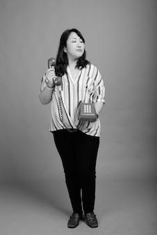 Studio shot di matura bella donna giapponese contro il grigio in bianco e nero