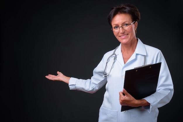 Studio shot di maturo bella donna scandinava medico con i capelli corti su sfondo nero