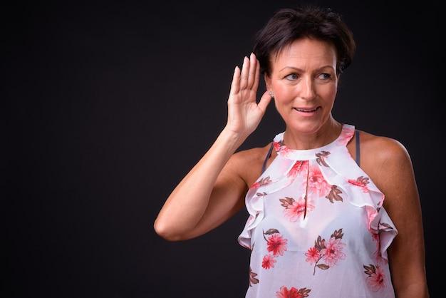 Studio shot di matura bella donna scandinava con i capelli corti su sfondo nero