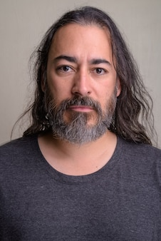 Colpo dello studio dell'uomo multietnico barbuto bello maturo con capelli lunghi