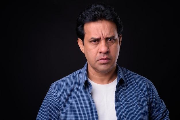 Studio shot di maturo bell'uomo indiano su sfondo nero