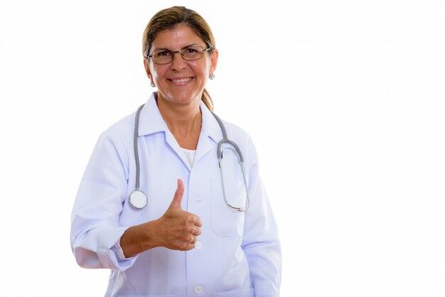 Colpo dello studio del medico maturo della donna felice che sorride mentre dà il pollice in su