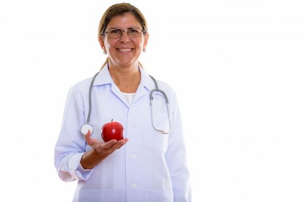 Studio shot di maturo donna felice medico sorridente mentre si tiene una mela rossa
