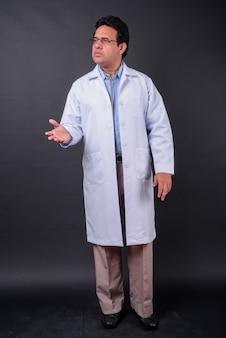 Studio shot di maturo uomo indiano medico su sfondo nero