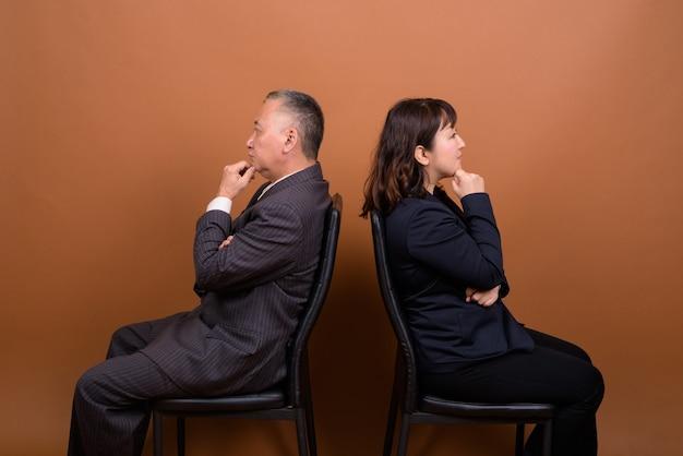 Studio shot di maturo giapponese imprenditore e maturo giapponese imprenditrice insieme su sfondo marrone