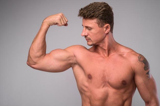 Colpo dello studio dell'uomo barbuto bello muscoloso torso nudo contro bianco