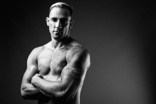Studio shot di uomo muscoloso torso nudo in bianco e nero