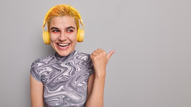 Studio shot di un adolescente alla moda ottimista con acconciatura alla moda trucco vivido ascolta podcast audio indica che il pollice lontano dimostra lo spazio della copia