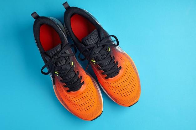Un colpo di studio di scarpe da ginnastica arancioni su sfondo blu. vista dall'alto