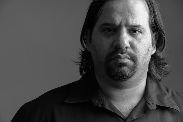 Studio shot di sovrappeso uomo barbuto isolato su uno sfondo grigio in bianco e nero