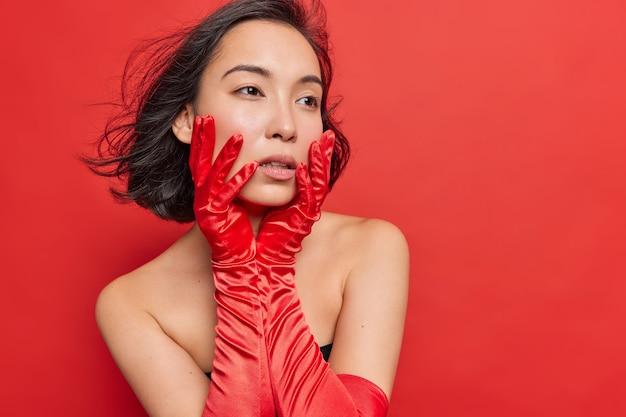 Studio shot di pensosa bella signora asiatica tiene le mani sul viso concentrate lontano indossa lunghi guanti rossi sta in piedi spalle nude pose indoor ha i capelli scuri lusingati in aria