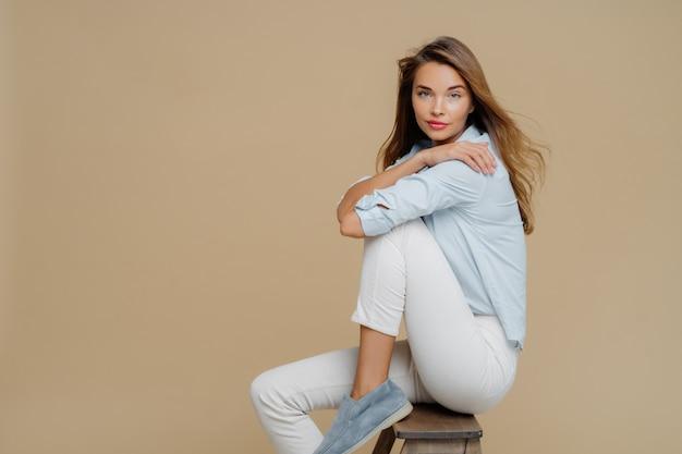 Lo studio ha sparato di bella donna caucasica riposante si siede sulla sedia, indossa camicia, pantaloni bianchi e scarpe