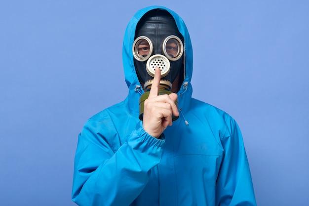 Colpo dello studio dell'uniforme d'uso e della maschera antigas dello scienziato, posare isolato sopra il blu