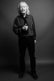 Studio shot dell'uomo d'affari senior con i baffi contro il muro grigio
