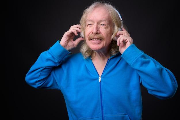 Studio shot di uomo anziano con i baffi ascoltando musica su sfondo grigio