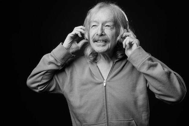 Studio shot di un uomo anziano con i baffi che ascolta la musica contro il muro grigio