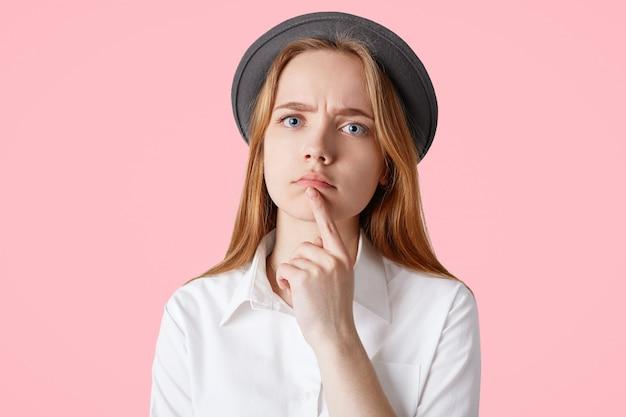 Lo studio ha sparato di una bella femmina dagli occhi blu seria con un aspetto attraente, indossa un elegante cappello nero e camicia bianca, tiene il dito anteriore sul mento, isolato su un muro rosa splendida signora caucasica