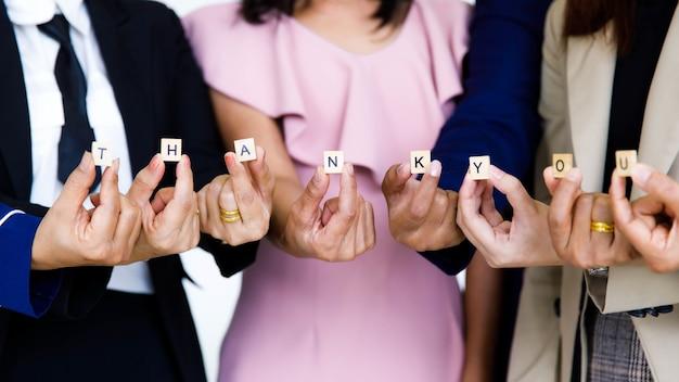 Studio shot di piccolo cubo di legno blocco grazie lettere alfabeti tenendo da personale ufficiale femminile senza volto non identificato irriconoscibile in affari indossa mostra apprezzamento per i colleghi dei clienti.