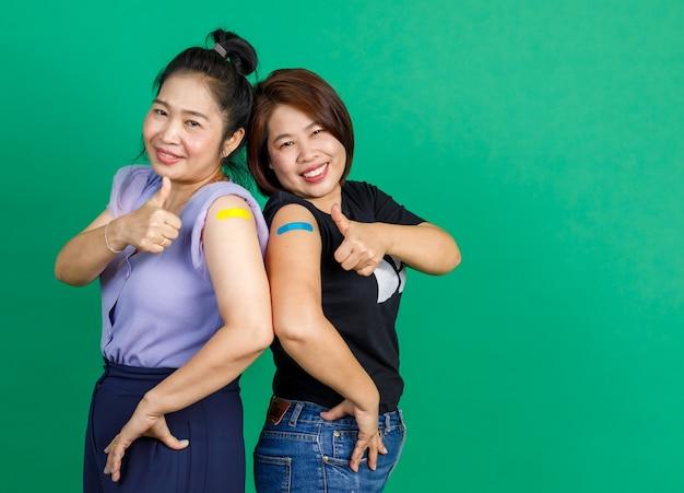 Studio shot di due amiche pazienti asiatiche di mezza età felici in piedi sorridenti guardano la telecamera che mostra il pollice in su con l'intonaco della fasciatura dopo aver ricevuto il vaccino contro il coronavirus covid 19 su sfondo verde.