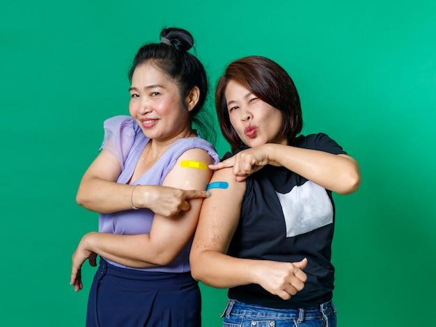 Studio scatto di due pazienti di sesso femminile di mezza età asiatiche felici indossano una maschera facciale in piedi guardano la telecamera che mostra il pollice in alto che indica un cerotto colorato per bende dopo aver ricevuto il vaccino contro il coronavirus covid 19