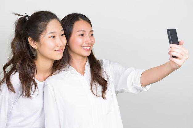 Studio shot di due giovani belle donne coreane come amici insieme su sfondo bianco