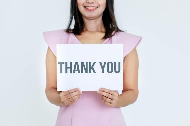 Studio shot di ufficiale femminile senza volto non identificato irriconoscibile in abiti da lavoro con cartello di carta di ringraziamento sul petto che mostra apprezzamento per i clienti e i colleghi su sfondo bianco.