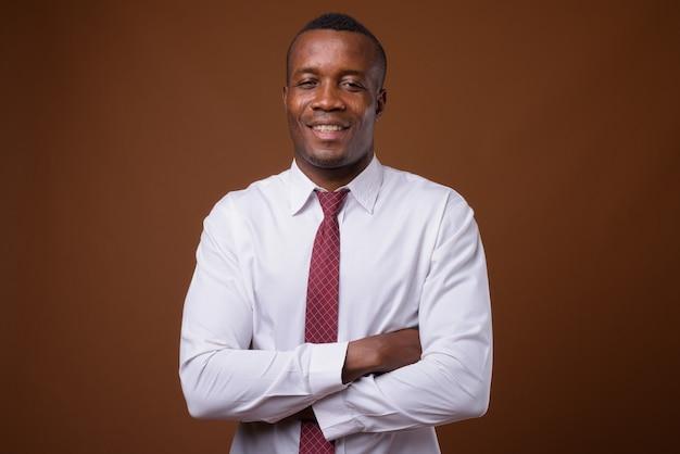 Studio shot di giovane imprenditore africano su sfondo marrone