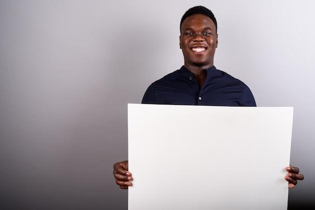 Studio shot di giovane imprenditore africano tenendo il bordo bianco su sfondo bianco
