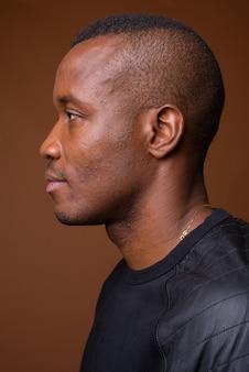 Studio shot di giovane uomo africano su sfondo marrone
