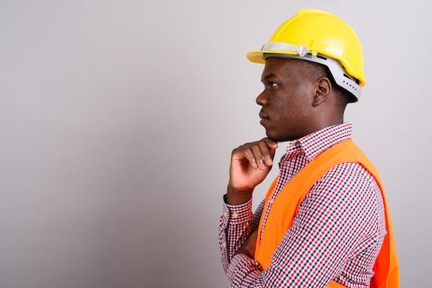 Studio shot di giovane operaio edile uomo africano su sfondo bianco