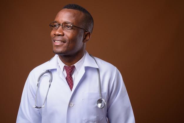 Studio shot di giovane uomo africano medico su sfondo marrone
