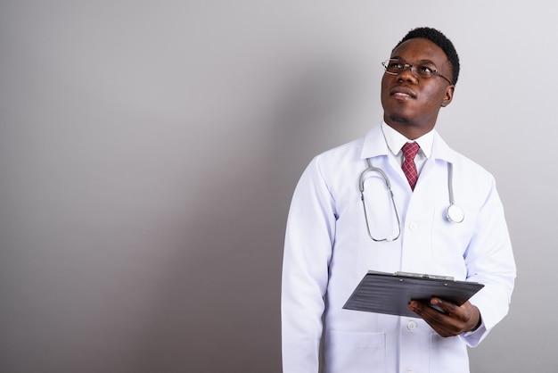 Studio shot di giovane africano medico uomo che indossa occhiali da vista mentre si tiene appunti su sfondo bianco