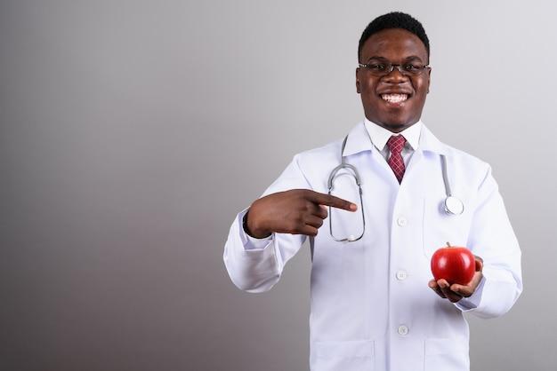 Studio shot di giovane uomo africano medico indossando occhiali da vista mentre si tiene la mela rossa su sfondo bianco