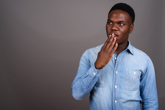 Studio shot del giovane africano che indossa la camicia in denim su sfondo grigio