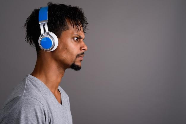 Studio shot di giovane barbuto bell'uomo africano ascoltando musica su sfondo grigio
