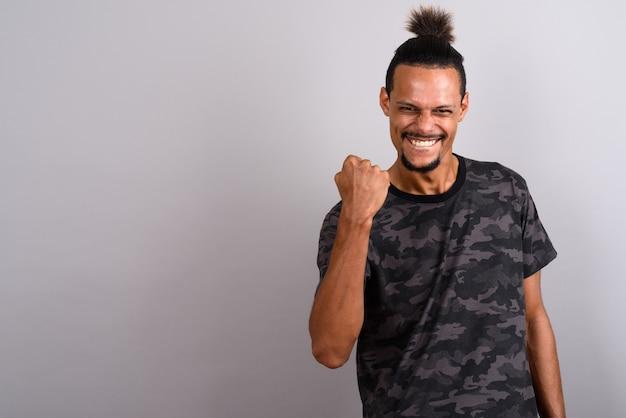 Studio shot di giovane barbuto bello africano uomo che indossa camouflage stampato maglietta con i capelli legati contro uno sfondo grigio
