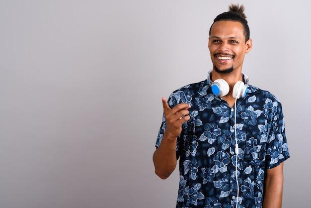 Studio shot di giovane barbuto bello africano uomo che indossa camicia hawaiana e cuffie su sfondo grigio