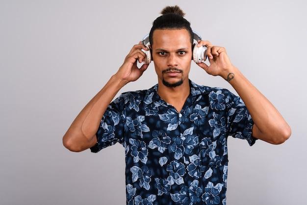Studio shot di giovani barbuti bell'uomo africano che indossa camicia hawaiana mentre si ascolta la musica su sfondo grigio