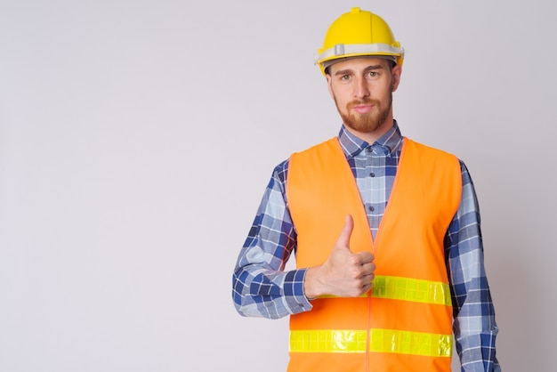 Studio shot di giovane uomo barbuto operaio edile contro bianco