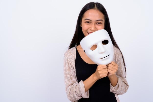 Studio shot di giovane bella donna asiatica su sfondo bianco