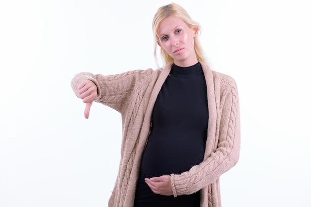 Studio shot di giovane bella donna incinta con i capelli biondi isolato su sfondo bianco
