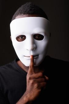 Studio shot di giovane uomo africano nero in camera oscura che indossa la maschera