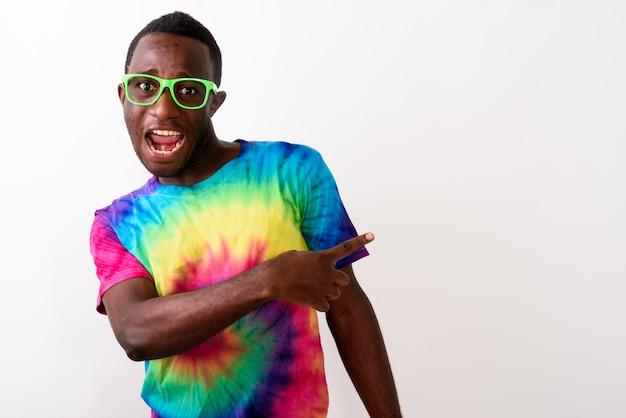 Studio shot del giovane africano nero uomo puntare il dito e showi