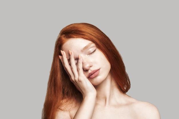 Studio shot di una giovane adolescente frustrata con lunghi capelli rossi che tiene gli occhi chiusi e si tocca il viso mentre si trova su sfondo grigio. malattia. emozioni umane