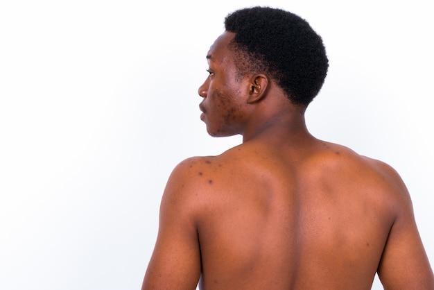 Studio shot di giovane uomo africano bello a torso nudo su sfondo bianco
