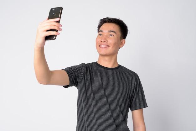 Studio shot di bel giovane uomo asiatico su sfondo bianco