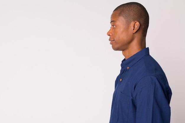 Studio shot di giovane uomo d'affari africano calvo bello su sfondo bianco
