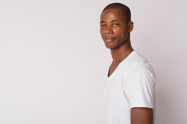 Studio shot di bel giovane uomo africano calvo su sfondo bianco