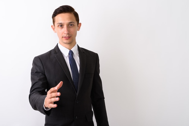 Studio shot di giovane uomo d'affari bello dando di nuovo la stretta di mano