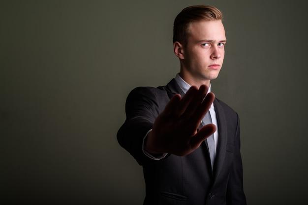 Studio shot di giovane uomo d'affari bello che indossa tuta su sfondo colorato